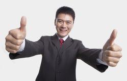 Усмехаясь счастливый бизнесмен давая большие пальцы руки-вверх с обеими руками к камере, съемке студии Стоковая Фотография RF