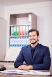 Усмехаясь счастливый предприниматель в деловом костюме на его месте работы Стоковая Фотография