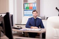 Усмехаясь счастливый предприниматель в деловом костюме на его месте работы Стоковое Фото