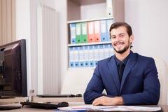 Усмехаясь счастливый предприниматель в деловом костюме на его месте работы Стоковые Изображения RF