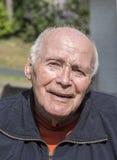 Усмехаясь счастливый старший человек сидя в его саде Стоковое фото RF