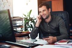 Усмехаясь счеты бизнесмена оплачивая над телефоном в офисе Стоковые Фото
