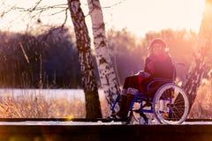 Усмехаясь с ограниченными возможностями женщина на кресло-коляске в зиме стоковое изображение rf