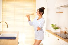 Усмехаясь танцы девушки в кухне стоковое изображение