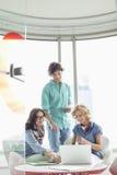 Усмехаясь творческие предприниматели обсуждая над компьтер-книжкой в офисе Стоковое Фото