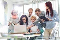 Усмехаясь творческие предприниматели работая на компьтер-книжке на столе в офисе Стоковые Изображения RF