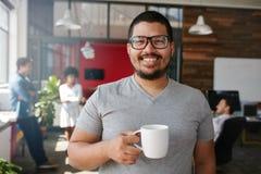 Усмехаясь творческое профессиональное имеющ кофе в офисе Стоковая Фотография RF