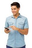 Усмехаясь текстовое сообщение чтения человека на умном телефоне стоковое фото