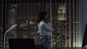 Усмехаясь телефон женщины говоря в офисе Стоковые Фотографии RF