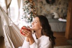 Усмехаясь темн-с волосами девушка одетая в бежевых свитере и брюках держит красную чашку сидя в гамаке в уютном украшенный стоковые фотографии rf
