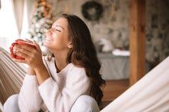 Усмехаясь темн-с волосами девушка одетая в бежевых свитере и брюках держит красную чашку сидя в гамаке в уютном украшенный стоковые фото