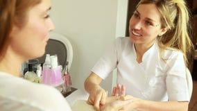 Усмехаясь терапевт красоты массажируя руки клиентов сток-видео
