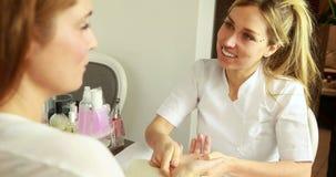 Усмехаясь терапевт красоты массажируя руки клиентов акции видеоматериалы