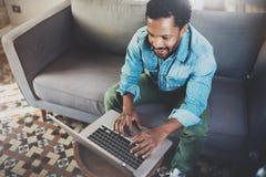 Усмехаясь тетрадь бородатого африканского человека работая дома пока сидящ на софе Концепция молодые люди используя чернь Стоковые Фото