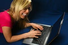 Усмехаясь типы женщины на компьтер-книжке Стоковое Фото