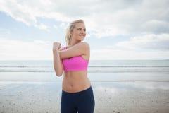 Усмехаясь тонизированная женщина работая на пляже Стоковые Изображения