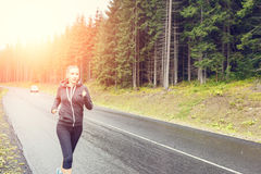 Усмехаясь тонкая женщина jogging на ненастном утре Стоковые Изображения