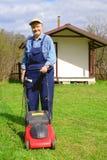 Усмехаясь трава вырезывания старика используя травокосилку Стоковая Фотография RF