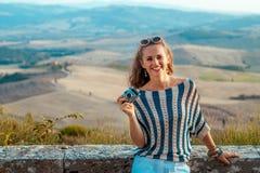 Усмехаясь туристская женщина с ретро камерой фото в Тоскане стоковая фотография