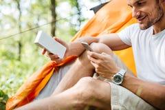 Усмехаясь турист человека используя мобильный телефон и портативный мини диктора Стоковое фото RF