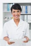 Усмехаясь уверенно женский доктор на медицинском офисе Стоковые Изображения RF