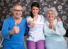 Усмехаясь удовлетворенное престарелое с медсестрой Стоковое Фото