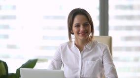 Усмехаясь успешная тысячелетняя коммерсантка смотря камеру на рабочем месте сток-видео