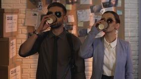 Усмехаясь успешные специалисты по исследования с кофейными чашками, качественным сервисом акции видеоматериалы
