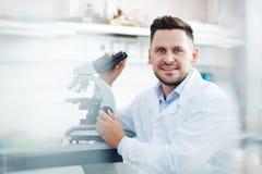 Усмехаясь ученый используя микроскоп в лаборатории Стоковые Фотографии RF