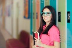 Усмехаясь учитель держа книгу в прихожей школы стоковое фото