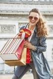Усмехаясь ультрамодная женщина с хозяйственными сумками в Париже, Франции Стоковое фото RF