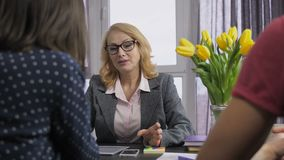 Усмехаясь финансовый консультант говоря к клиентам сток-видео