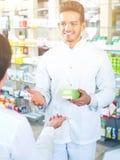 Усмехаясь форма аптекаря человека нося помогая клиентам Стоковое Изображение RF