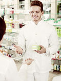 Усмехаясь форма аптекаря человека нося помогая клиентам Стоковая Фотография