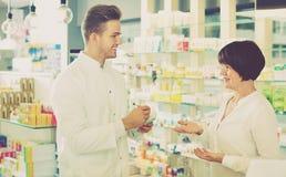 Усмехаясь форма аптекаря человека нося помогая клиентам Стоковое Фото