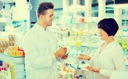 Усмехаясь форма аптекаря человека нося помогая клиентам Стоковые Изображения RF