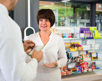 Усмехаясь форма аптекаря человека нося помогая клиентам Стоковые Фотографии RF