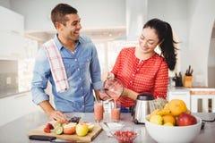 Усмехаясь фруктовый сок женщины лить в стекле при человек говоря к ей Стоковое Изображение RF