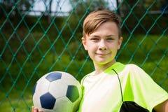 Усмехаясь футболист мальчика стоковые фото