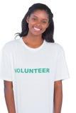 Усмехаясь футболка молодой женщины нося добровольная стоковая фотография rf
