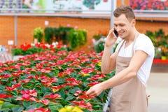 Усмехаясь флорист говорит на телефоне Стоковое фото RF