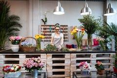 Усмехаясь флорист женщины стоя и работая в цветочном магазине Стоковые Изображения