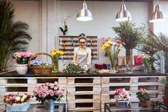 Усмехаясь флорист женщины стоя и работая в цветочном магазине Стоковая Фотография