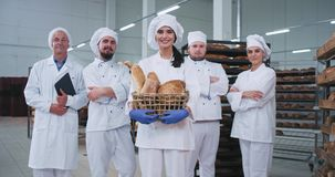 Усмехаясь харизматический хлебопек молодой дамы и полностью главная команда хлебопека в середине производства пекарни смотря прям сток-видео