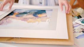 Усмехаясь художник представляя картину акварели рамки сток-видео