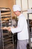 Усмехаясь хлебопек держа поднос хлеба Стоковая Фотография RF