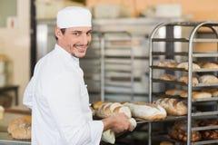 Усмехаясь хлебопек держа поднос хлеба Стоковое фото RF