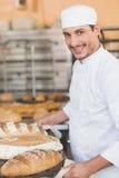 Усмехаясь хлебопек держа поднос хлеба Стоковые Изображения RF