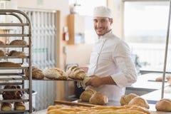 Усмехаясь хлебопек держа поднос хлеба Стоковые Изображения