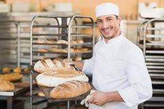 Усмехаясь хлебопек держа поднос хлеба Стоковые Фотографии RF